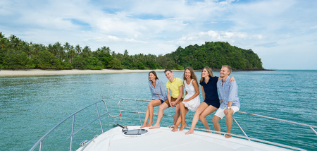 Tropic vacation. Group of young beautiful people smiling on the yacht Standard-Bild