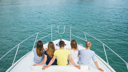 rich people: Group of young people siting and looking outside from yacht. Back view.