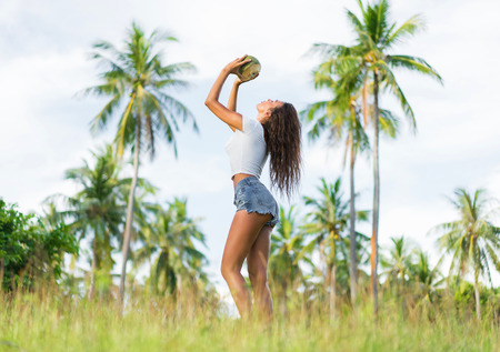 Young beautiful woman drink coconut juice between palms.