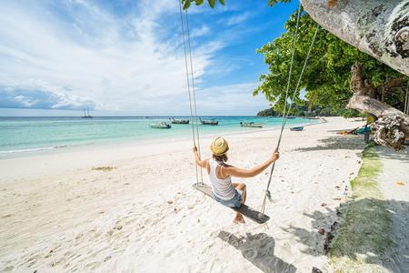 Beautiful woman swinging on a Tropical beach on Koh Lipe island. Thailand.