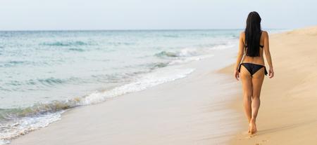 Urlaub auf dem Meer. Junge sexy kaukasischen Frau zu Fuß am Ozean Strand. Zurück weiten Blick.