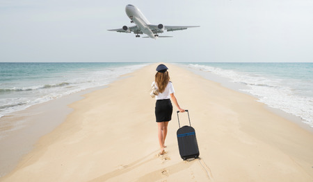 Travel concept. Young woman in flight attendant clothes walking on the beach with suitcase and hat. Overhead fly plane.
