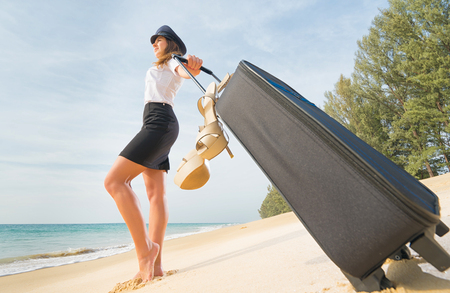 flight crew: Travel concept. Attractive flight attendant with suitcase, hat and shoes on the beach. Stock Photo