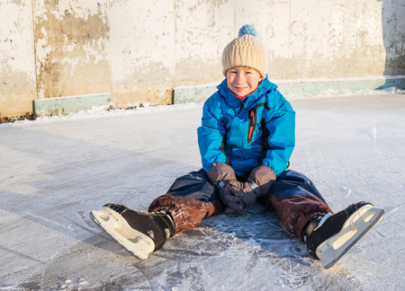ange: Child with skates sits and have fun in the outdoor rink. Wide ange close up shoot.