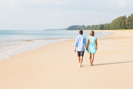 walking away: Back view of loving couple walking away on sandy beach Stock Photo