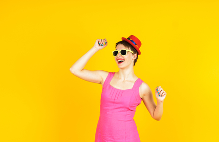 funy: young woman dancing in sunglasses and small funy hat on yellow background