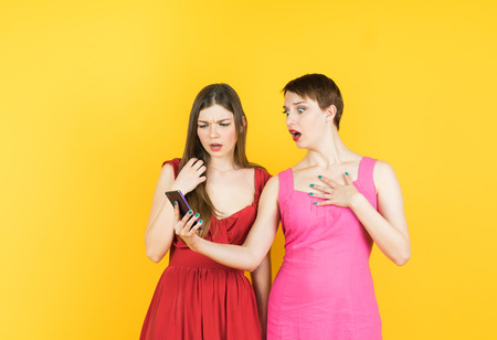 bummed: Two shocked women looking at mobile phone seeing bad news message or photos with disgusting emotion on face. Human emotion, reaction, expression. Isolated studio yellow background female model.