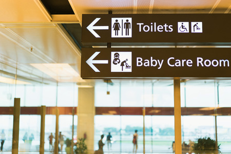 Toilets icon. Public restroom signs with a disabled access symbol, baby care room. Interior of airport terminal.