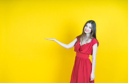advertise: Your text here. Colorful studio portrait of young smiling woman pointing copy space. yellow background.