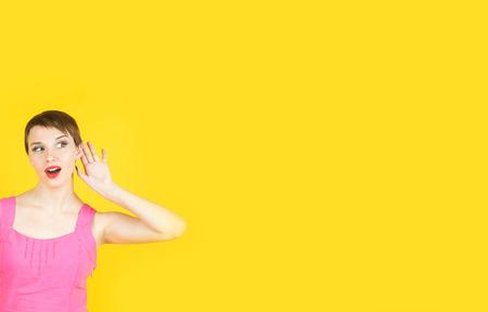 chismes: Concepto de chismes. retrato de estudio colorido de la mujer joven y bonita con la palma cerca de la oreja.