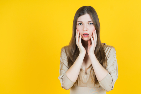 girl mouth: Portrait of surprised beautiful girl holding her head in amazement and open-mouthed. Over yellow background.