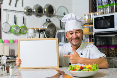 Portrait of smiling asian chef  with white board for your text on kitchen background