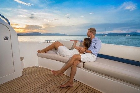 riches: Romantic vacation . Beautiful couple looking in sunset from the yacht