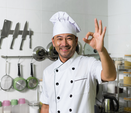 Asian chef smiling and showing OK on the kitchen background. Focus on face. Hand blured.