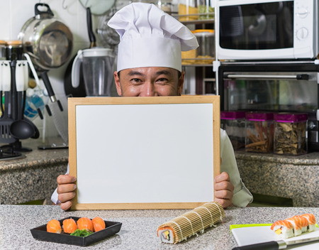 front desk: Happy smiling asian chef hold white desk with sushi and rolls on the front. Kitchen background.