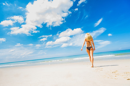 Tropical vacation. Young beautiful woman walking alone on the beach. Back view. Wide angle shoot.