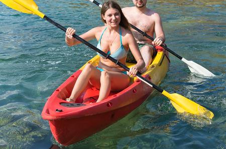 exploring: Couple exploring calm tropical bay by kayak.