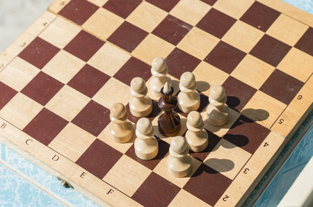 uprising: Black king and white pawns on the old chess board.