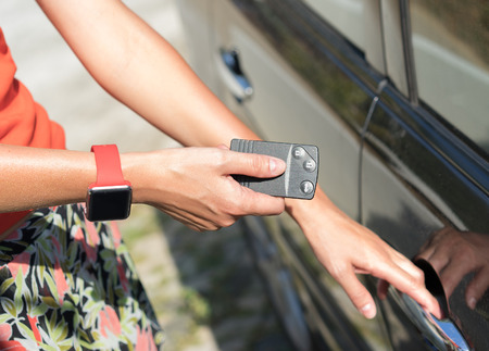 women's hand: womens hand with smart watch presses on the remote control car alarm systems