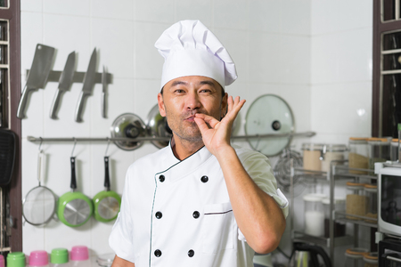 asian cook: Asian chef smiling and showing delicious on the kitchen background.