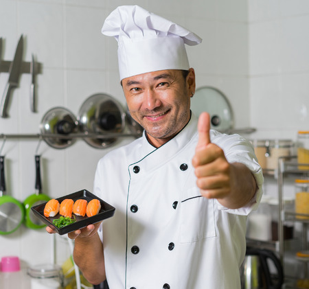 Asian chef sgowing plate with sushi and OK. Focus on sushi. Stock Photo