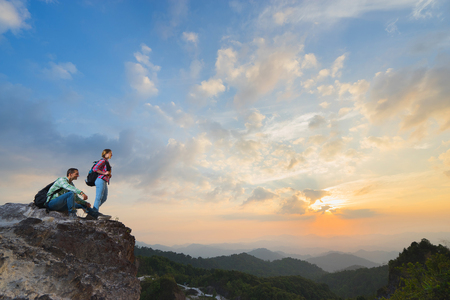 valley view: Young backpackers enjoying a valley view from top of a mountain in sunset. Travel concept.