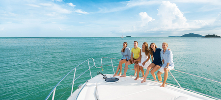 Luxury vacation. Group of young beautiful people smiling on the yacht. Banner.
