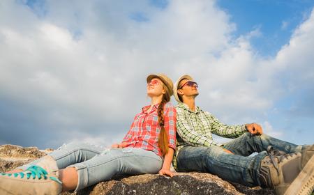 taking a break: Happy Couple hiking taking a break sitting on mountain top.
