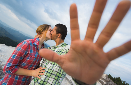 shielding: Young couple kissing on the top of mountain  and man is shielding with his arm