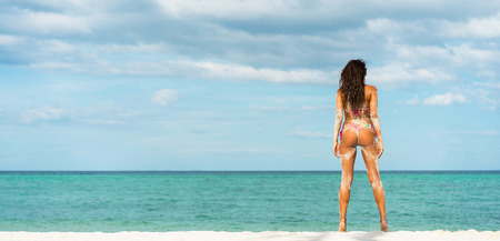 beach panorama: Beach vacation. Hot beautiful woman in bikini standing and  enjoying looking view of beach ocean on hot summer day. Banner