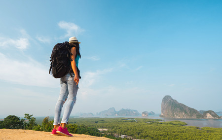 valley view: Hiker with backpack standing on top of the mountain and enjoying valley view Stock Photo
