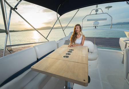 adult cruise: Luxury traveling and vacation. Young beautiful woman on the yacht at sunset time.