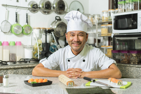 Smiling asian chef  with kitchen background. Focus on the face.