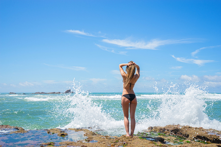 marocco: Young beautiful woman standing on the stones nearly waves splash with sea and sky background. Stock Photo