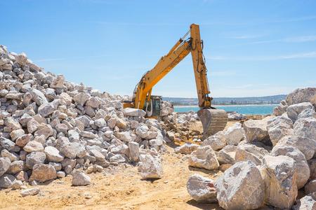 Mechanical excavator working on coast with big stones.