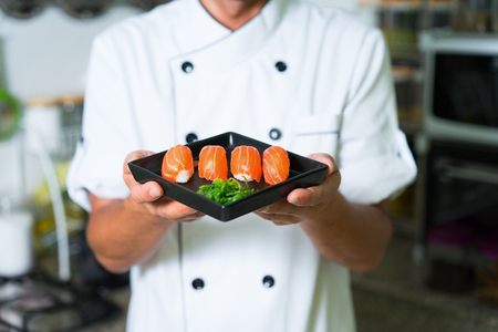 Close up Sushi in chefs hands. Focus on sushi Stock Photo