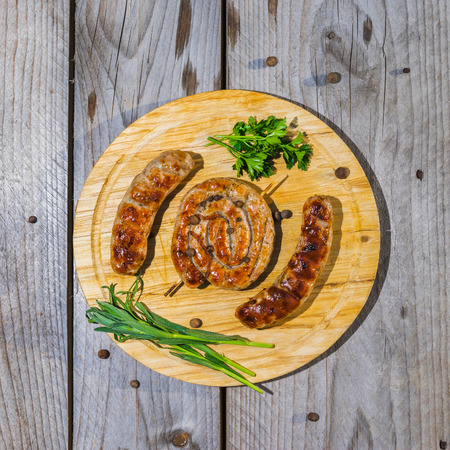 weisswurst: Grilled sausages served on wooden plate over wooden table. Overhead close up shot.