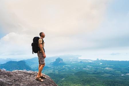 Wandelaar met packpack die zich bevindt en van een mooie aard vanaf bovenkant van berg geniet. Thailand. Krabi. Stockfoto