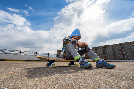 skate park: Boy sitting on skateboard and thinking about something