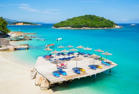 sunshade: Sunshade umbrellas and  deckchairs  on the beautiful Ksamil beach, Albania. Stock Photo