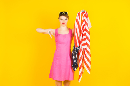 Young  woman with american flag in hand shows bad with another hand Stock Photo