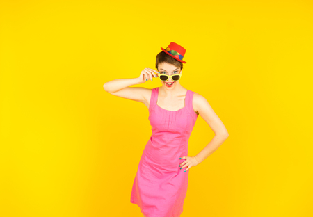 Young woman in sunglasses and small funy hat on yellow background