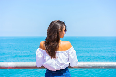 Young beautiful woman looking on sea and sky. Back view.