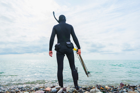 speargun: Underwater hunter on the beach preparing to dive. Underwater fishing in the Black sea .