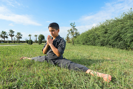 Boy in kimono training karate in the park.  Meditation pose. Standard-Bild