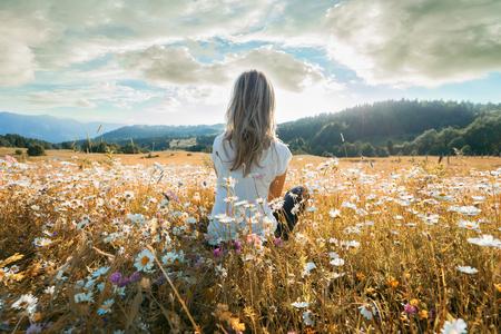 Jonge vrouw zittend op het chamomiles veld en kijkend naar de bewolkte hemel.