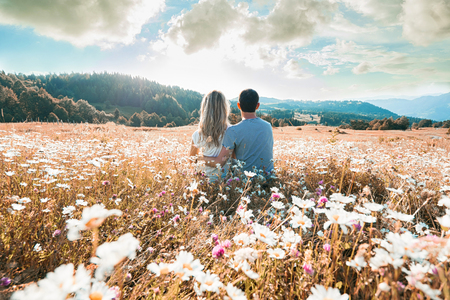Young couple sitting on the chamomiles field and looking at the cloudy sky. Back view. Stock Photo
