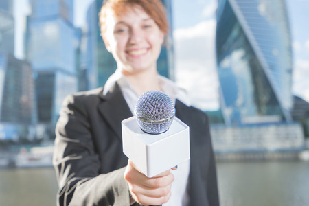 Smiling woman in business suit holding a microphone conducting a business interview, journalist reporting, public speaking, press conference, MC. Focus on the microphone. Woman and skyscrapers blured.
