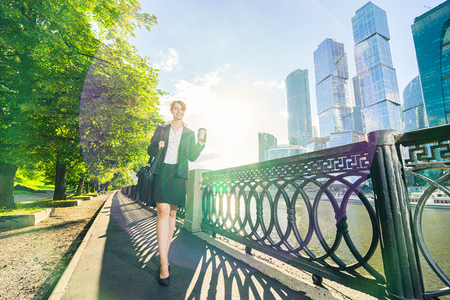 Young business woman walking in the park with coffee cup and bag with skyscrapers on background. Stock Photo
