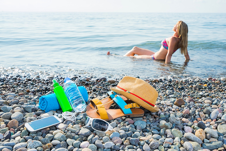 suncream: Vacation concept. Essentials on the sea beach with blured relaxing woman in sea on background. Bottle of drinking water, sunglasses, hat, shoes, suncream, towel, mobile.